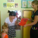 Воспитатель беседует с мамой, держащей за руку девочку