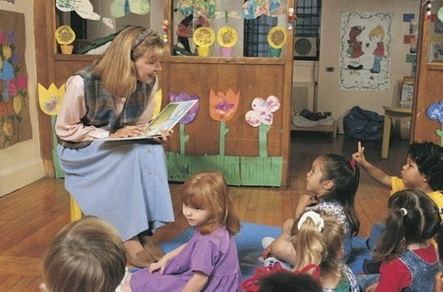 Воспитатель эмоционально читает малышам книгу