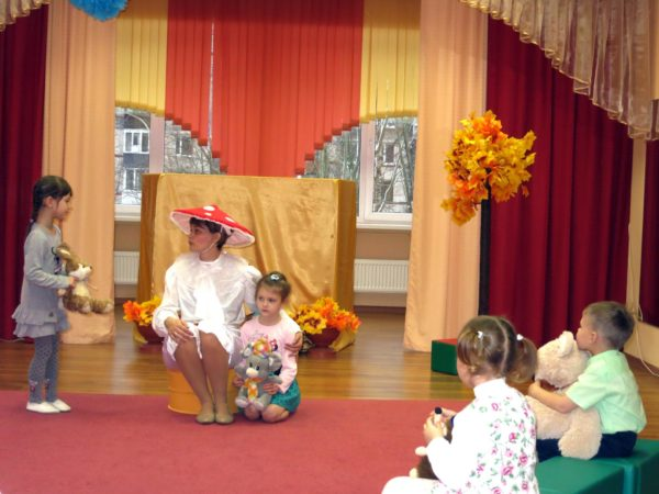 Воспитательница в костюме мухомора, дети в игрушками в руках возле неё