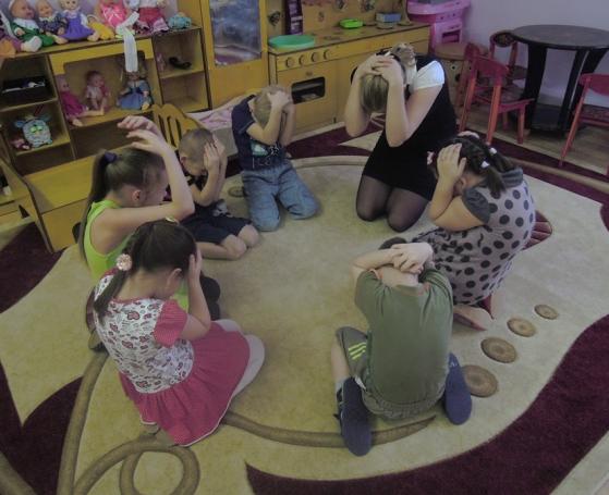 Воспитательница и дети обхватили голову руками, сидят на коленях на полу