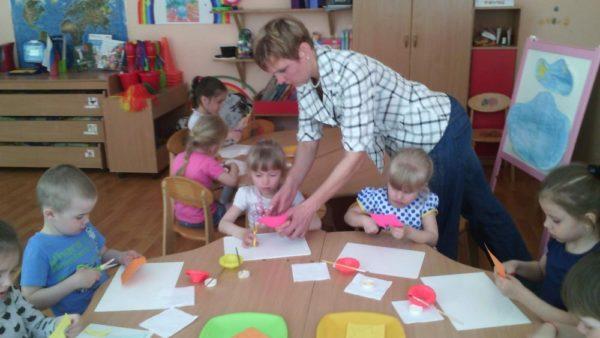 Воспитательница помогает детям делать аппликацию