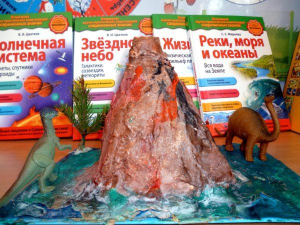 Макет вулкана в окружении пальмы и динозавров, на заднем плане — книги