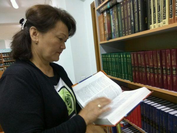 Женщина стоит у книжного шкафа и читает книгу