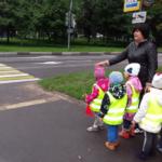 Воспитатель ведёт группу детей к пешеходному переходу