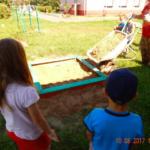 Дети наблюдают, как мужчина наполняет песочницу песком