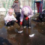 Дети пускают кораблики в луже ранней весной
