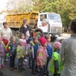 Группа детей и воспитатели смотрят на самосвал