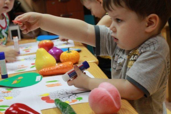 Дети занимаются аппликацией, на столах лежат муляжи овощей и фруктов