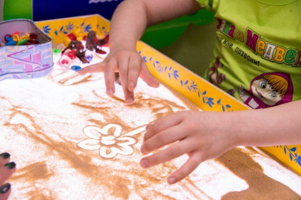 Ребёнок создаёт изображение цветка с помощью песка
