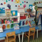 Центр творчества, синие столики, деревянные стулья, на полочках над столами материалы и готовые рисунки