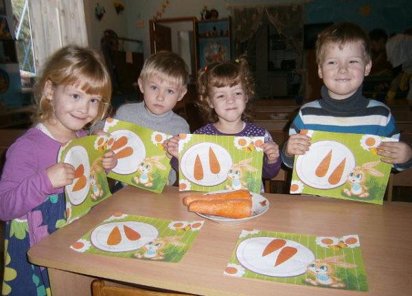 Четверо детей сидят за столом, держа в руках изображения морковок