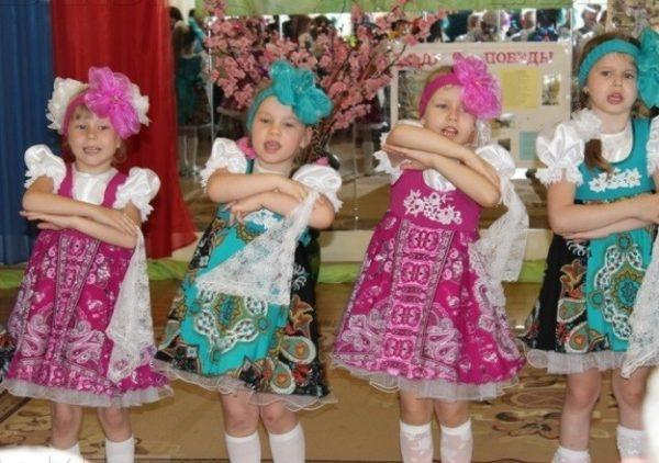 Четыре девочки в народных костюмах танцуют и поют