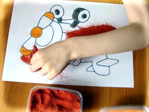 Ребёнок раскрашивает рисунок цветным песком