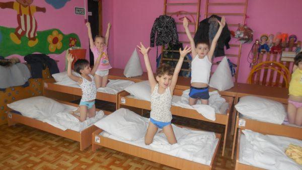 Дети делают гимнастику после сна в кроватях