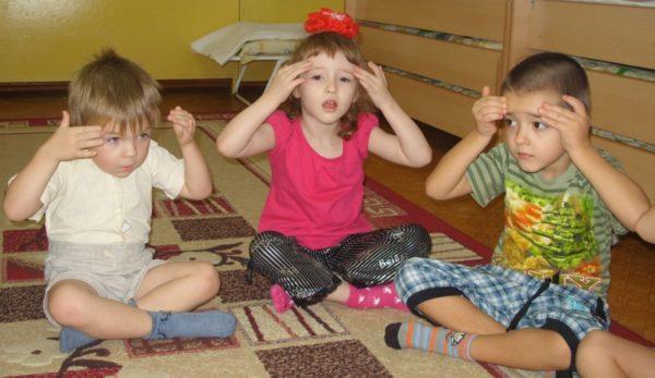 Два мальчика и девочка, сидя на ковре, делают самомассаж