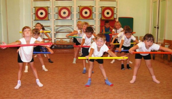 Дети выполняют упражнение с обручами в спортивном зале