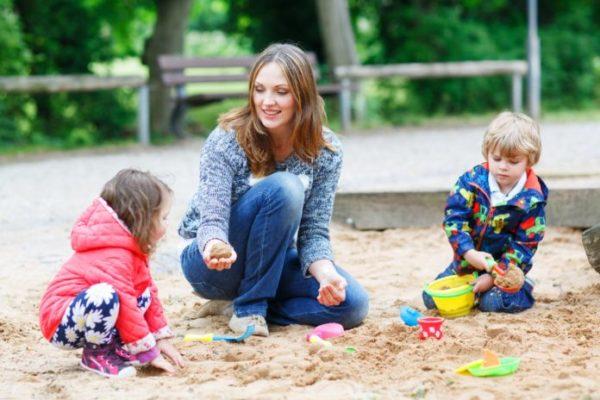 Два ребёнка и воспитатель играют в песочнице