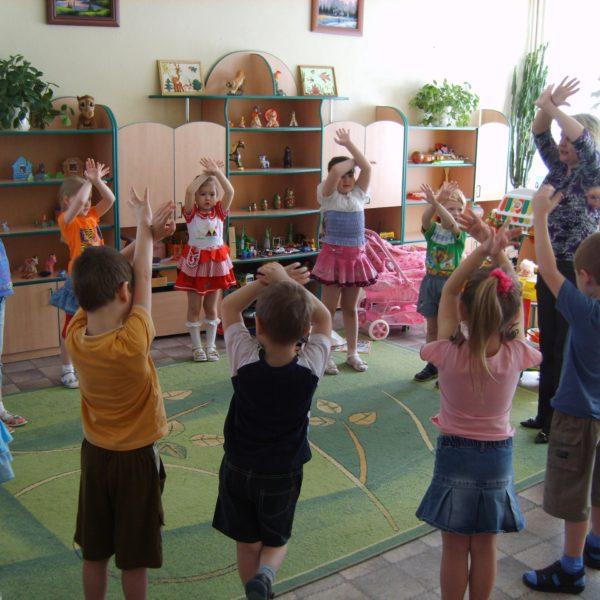 Дети и воспитатель стоят с поднятыми вверх руками