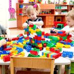 Дети играют с конструктором, сидя за столом