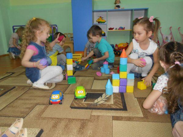 Дети играют с конструктором, сидя на ковре