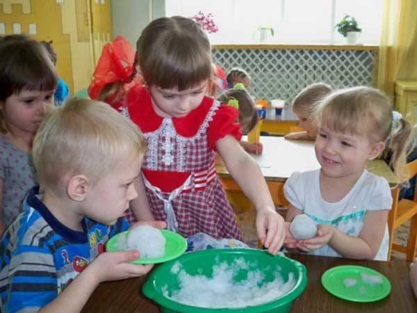 Дети играют со снегом в помещении группы