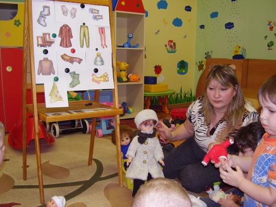Дети и воспитатель играют в игру «Одень куклу»