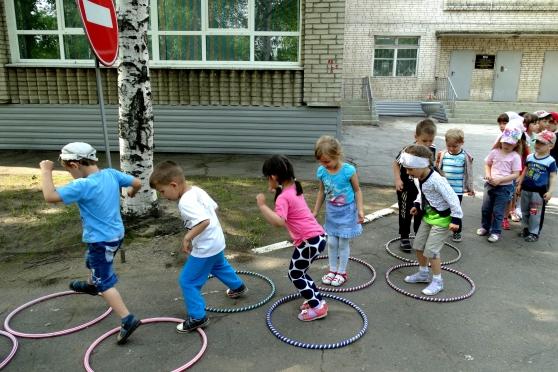 Дети на улице играют в подвижную игру с обучами