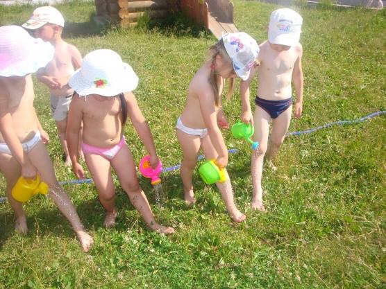 Дети в жару льют воду себе на ноги из леек