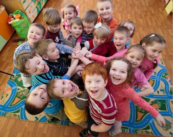 Группа улыбающихся детей, стоящих плотно друг к другу