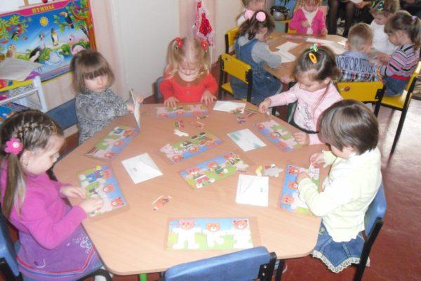 Дети, сидя за столами, подбирают бумажную одежду для изображений медведей