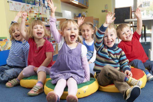 Дети сидят на ковре, улыбаясь и подняв руки