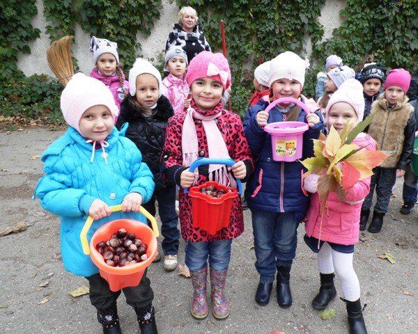 Дети стоят на улице с вёдрами, наполненными каштанами