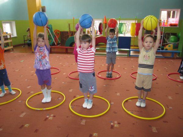 Дети стоят с мячами в руках, поднятыми над головой