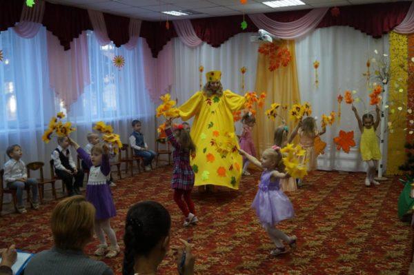 Дети и педагог в жёлтом костюме танцуют с осенними листьми