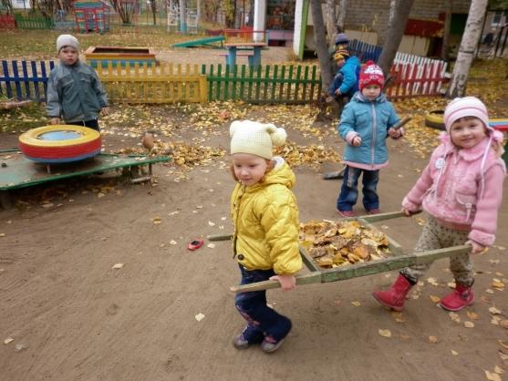 Дети собирают опавшие листья на площадке осенью