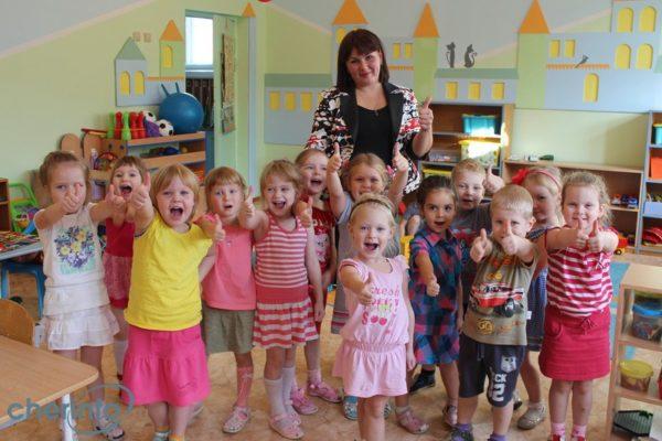 Дети в группе стоят с воспитательницей, показывают одобряющий жест