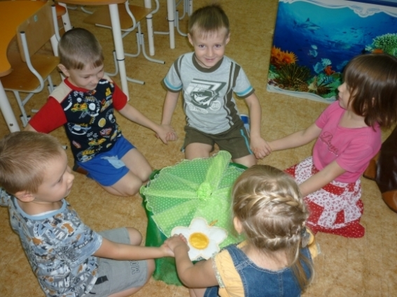 Дети сидят на полу, держась за руки