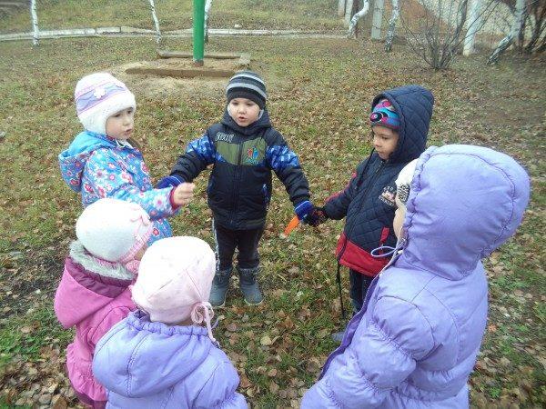 Дети в куртках стоят в кругу, держась за руки, на улице