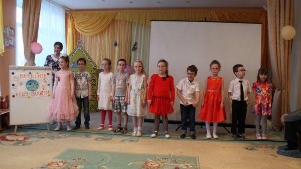 Дети в нарядных костюмах стоят на сцене рядом с плакатом о сохранении земли