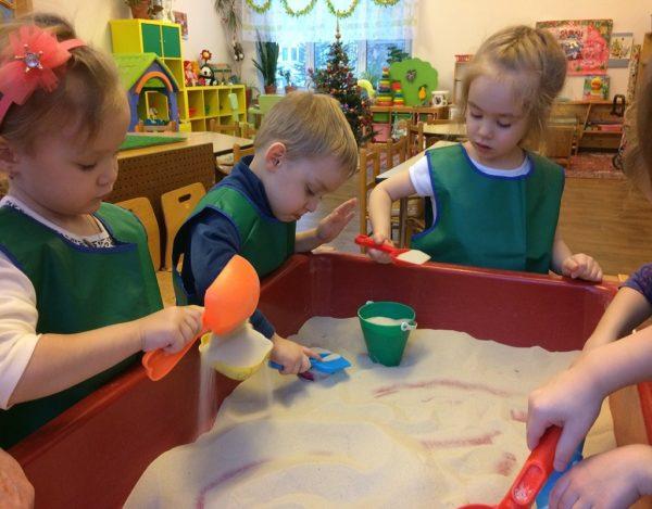 Дети в зелёных фартуках возятся в ящике с песком, стоящим в группе