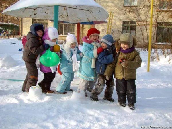 Дети выстроились друг за другом на снегу
