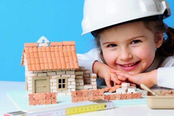Девочка в строительной каске рядом с недостроенным игрушечным домиком