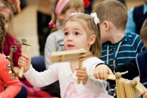 Девочка размахивает музыкальными инструментами