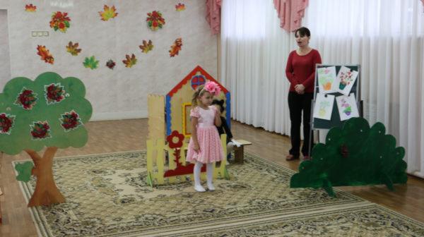 Девочка с розовым цветком на голове и воспитатель на фоне декораций — дерева, куста и домика на заднем плане