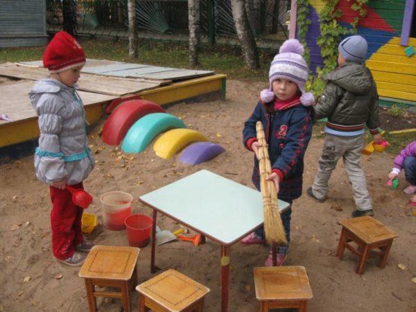 Девочка стоит с веником в руках, другие дети играют с песком