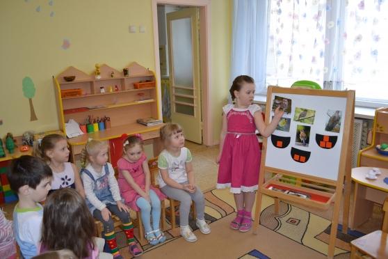 Девочка стоит у небольшой доски с размещёнными на ней изображениями птиц, остальные дети наблюдают