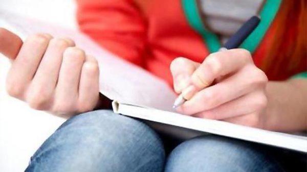 Девушка делает ручкой пометки в блокноте, лежащем на коленях