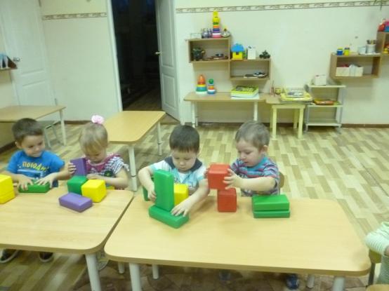 Четверо дошкольников, сидя за столами, делают конструкции из строительного материала
