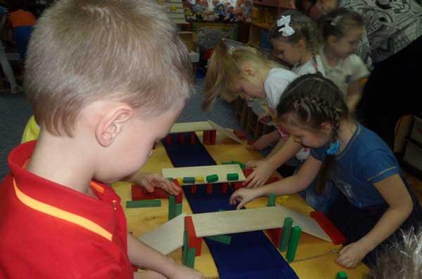 Дошкольники строят мосты из деталей деревянного конструктора