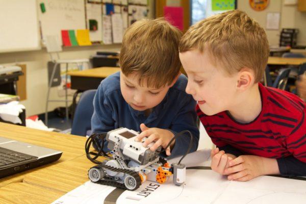 Два мальчика, сидя за столом, рассматривают какое-то техническое устройство